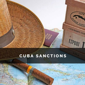 a straw hat, cigar, passport and a box of coffee on a map of Cuba