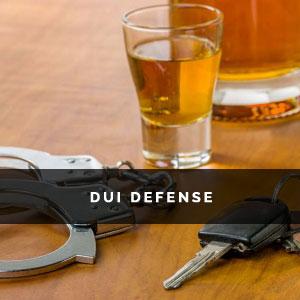 a shot glass, car keys and handcuffs