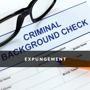 pair of reading glasses on top of a criminal background form.